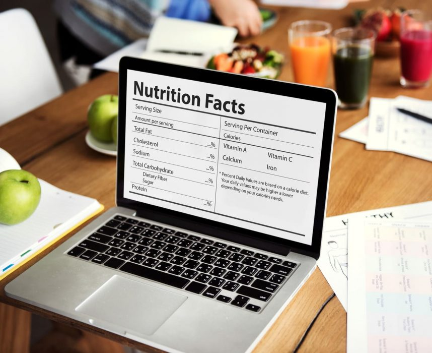 Laptop with nutrition fact on monitor, healthy food on the background